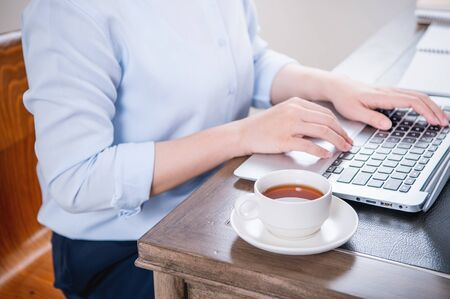 Business concept. Woman in blue shirt typing on computer with coffee on office table, backlighting, sun glare effect, close up, side view, copy space Reklamní fotografie