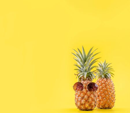 Creative pineapples with sunglasses isolated on yellow background Reklamní fotografie