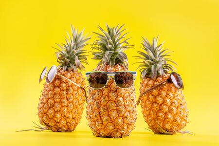 Creative pineapple with sunglasses isolated on yellow background