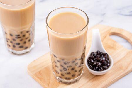 Popular Taiwanese tea-based drink - Bubble milk tea on wooden tray on white marble table Stock Photo - 124945409