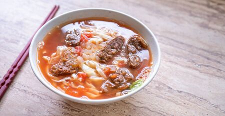 Beef noodle ramen meal with tomato sauce broth in bowl on bright wooden table, famous chinese style food in Taiwan, close up, top view, copy space 写真素材
