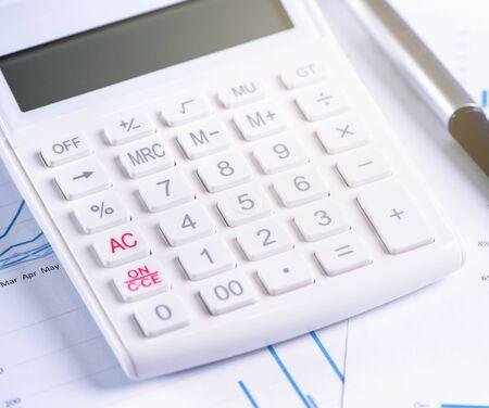 Biały kalkulator i raport z wykresem i wykresem, koncepcja rocznego przeglądu zysków finansowych, bankowości i inwestycji, miejsca kopiowania, makro, zbliżenie Zdjęcie Seryjne