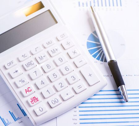 White calculator and report with chart and graph, concept of annual financial profit overview, banking and investment, copy space, macro, close up