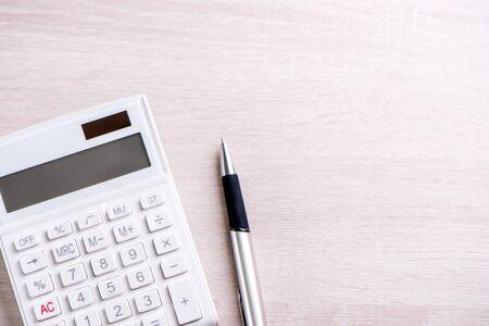 Calcolatrice bianca e penna su tavolo in legno brillante, analisi e statistiche di profitto finanziario, concetto di rischio di investimento, spazio copia, vista dall'alto piatta
