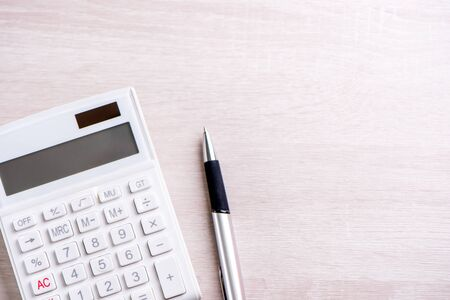 White calculator and pen on bright wooden table, analytics and statistics of financial profit, investment risk concept, copy space, top view flat lay Stockfoto