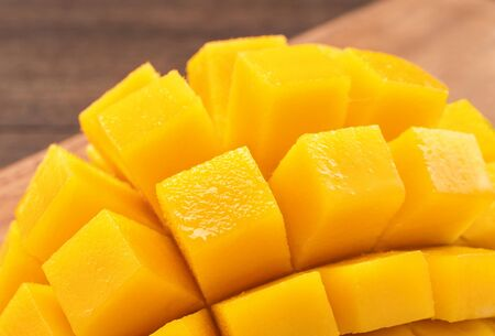 Fresh chopped mango cubes on wooden cutting board and rustic timber background. Tropical summer fruit concept, close up, macro, copy space.
