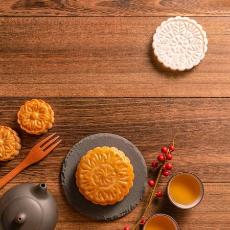 Chinese traditional mooncake with teacups on wooden background, Mid-Autumn Festival concept, top view, flat lay.