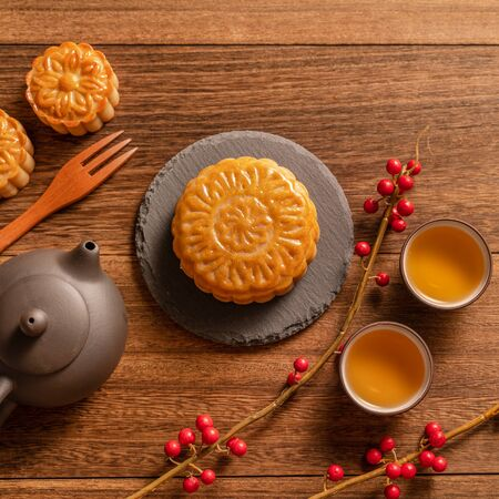 Moon cake Mooncake table setting - Chinese traditional pastry with tea cups on wooden background, Mid-Autumn Festival concept, top view, flat lay.