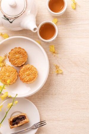 Delicious mooncake for Mid-Autumn festival, decorated with yellow flowers and tea.