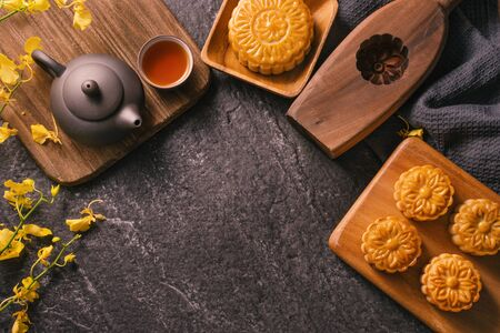 Mid-Autumn Festival traditional food concept - Beautiful Moon cake on black slate table with tea, pastry mold, flower, top view, flat lay, copy space