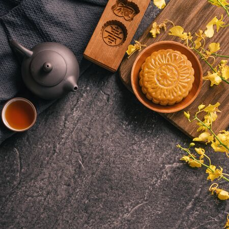 Mid-Autumn Festival traditional food concept - Mooncake on black slate table with tea, pastry mold, flower, top view, flat lay, copy space