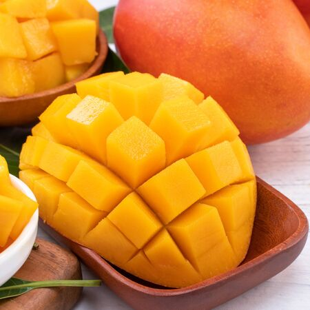 Fresh chopped mango on a tray and bright rustic wooden background. Tropical summer fruit design concept, close up, macro, copy space.