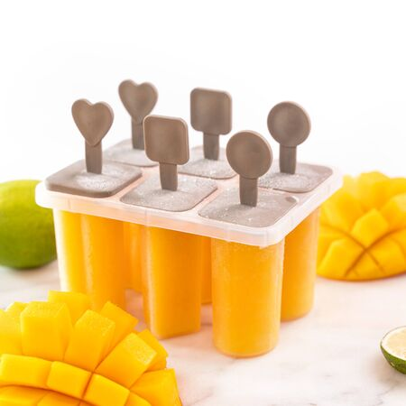 Fresh mango fruit ice stick in the plastic shaping box on bright marble table. Summer mood concept product design, close up. Reklamní fotografie