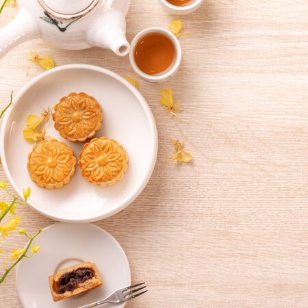 Tasty moon cake for Mid-Autumn festival on bright wooden table, concept of festive afternoon tea decorated with yellow flowers, top view, flat lay.