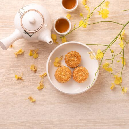 Tasty moon cake for Mid-Autumn festival on bright wooden table, concept of festive afternoon tea decorated with yellow flowers, top view, flat lay. Foto de archivo