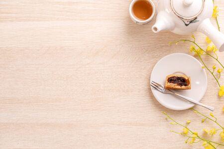 Sabroso pastel de luna para el festival de mediados de otoño en la mesa de madera brillante, concepto de té de la tarde festivo decorado con flores amarillas, vista superior, endecha plana. Foto de archivo