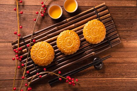Chinese traditional pastry Moon cake Mooncake with tea cups on bamboo serving tray on wooden background for Mid-Autumn Festival, top view, flat lay.
