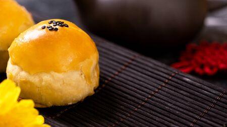 Tasty baked egg yolk pastry mooncake for Mid-Autumn Festival on black slate dark background. Chinese festive food concept,  copy space. Stok Fotoğraf