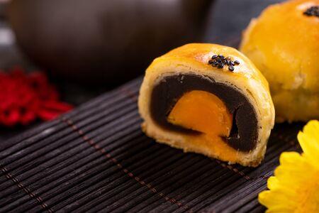 Tasty baked egg yolk pastry mooncake for Mid-Autumn Festival on black slate dark background. Chinese festive food concept, copy space.