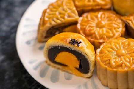 Tasty baked egg yolk pastry mooncake for Mid-Autumn Festival on black slate dark background. Chinese festive food concept, close up