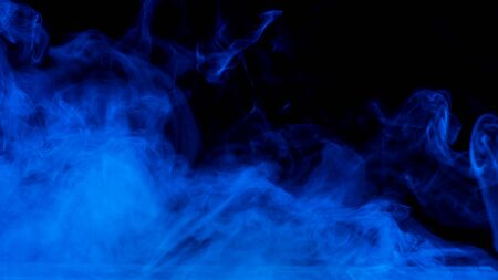 Conceptual image of blue smoke isolated on black background and wooden table.
