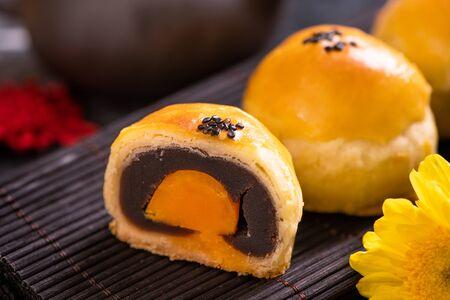 Tasty baked egg yolk pastry mooncake for Mid-Autumn Festival on black slate dark background. Chinese festive food concept