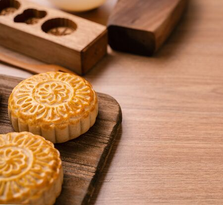 Freshly baked pastry - Chinese mooncakes for Mid-Autumn Festival on wooden background, copy space, close up