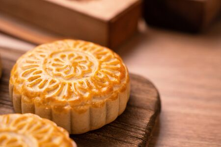 Freshly baked pastry - Chinese mooncakes for Mid-Autumn Festival on wooden background, close up