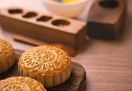 Freshly baked pastry - Chinese mooncakes for Mid-Autumn Festival on wooden background, copy space