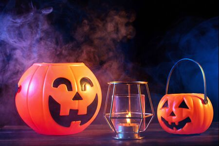 Halloween concept - Orange pumpkin lanterns on a dark wooden table with double colored smoke around the background, trick or treat, close up.