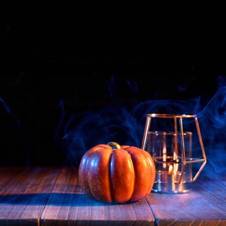 Halloween concept - Pumpkin on a dark wooden table with smoke around the background, trick or treat