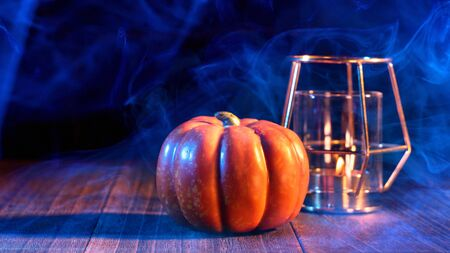 Halloween concept - Pumpkin on a dark wooden table with smoke around the background, trick or treat, close up.