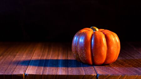 Halloween concept - Pumpkin on a dark wooden table with black background, trick or treat Stok Fotoğraf