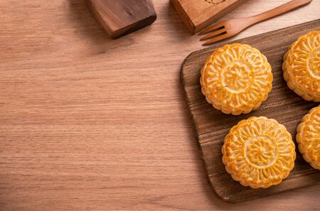 Freshly baked pastry - Chinese mooncakes for Mid-Autumn Festival on wooden background, copy space, top view, flat lay.