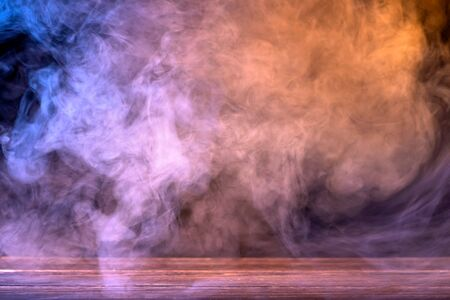 Conceptual image of multi-colored smoke isolated on dark background and wooden table.