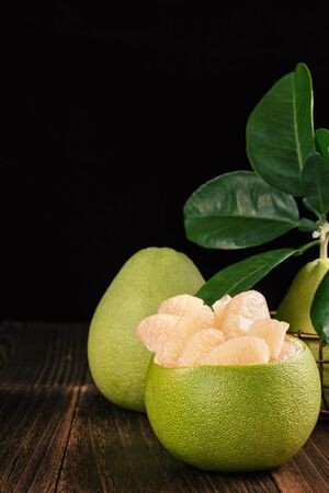 Fresh peeled pomelo, grapefruit, shaddock with green leaves on dark wooden plank table. Seasonal fruit near mid-autumn festival, close up, copy space Stock Photo
