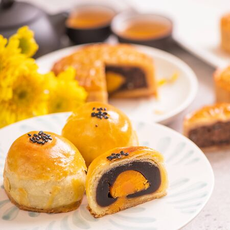 Mid-Autumn Festival traditional food concept - Beautiful cut moon cake on blue pattern plate on white background with flower, close up, copy space 版權商用圖片