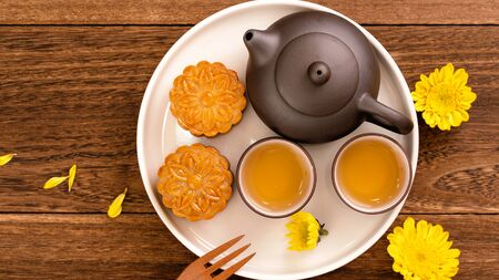 Mooncakes with tea on dark wooden table, holiday concept of Mid-Autumn festival traditional food layout, top view, flat lay, copy space.