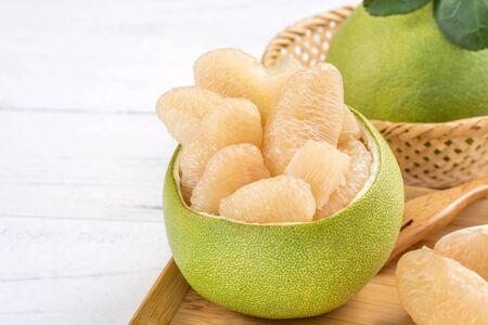 Pomelo fraîchement pelé sur une table en bois clair. Fruits de saison de la fête de la mi-automne, gros plan, espace de copie Banque d'images