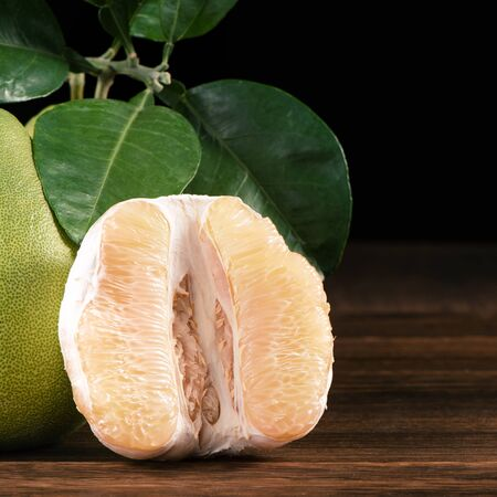 Fresh peeled pomelo, grapefruit, shaddock with green leaves on dark wooden plank table. Seasonal fruit near mid-autumn festival, close up, copy space Archivio Fotografico