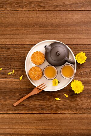 Mid-Autumn Festival mooncakes and tea set on wooden table with copy space, top view, flat lay