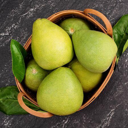 Pomelo frais, pamplemousse dans un panier en bambou avec feuille verte sur fond d'ardoise noire foncée. Fruits de saison pour la fête de la mi-automne. Vue de dessus. Mise à plat.