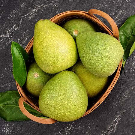 Fresh pomelo,grapefruit in bamboo basket with green leaf on dark black slate background. Seasonal fruit for Mid-Autumn Festival. Top view. Flat lay.