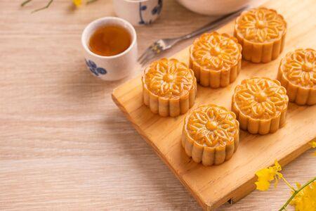 Diseño de concepto de vacaciones del Festival del Medio Otoño de pastel de luna, pasteles de luna, juego de té en la mesa de madera brillante y plato para servir con espacio de copia, de cerca.