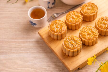 Mid-Autumn Festival holiday concept design of moon cake,mooncakes,tea set on bright wooden table and serving plate with copy space, close up.