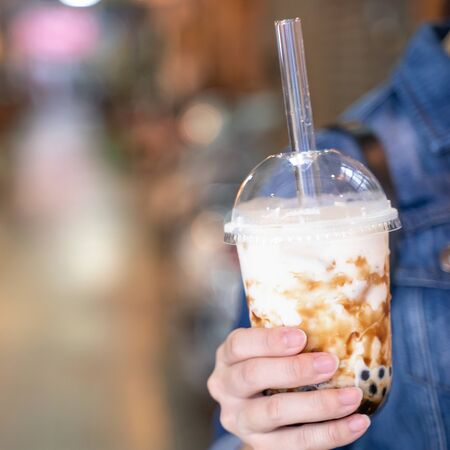 Young girl in denim jacket is drinking brown sugar flavored tapioca pearl bubble milk tea with glass straw in night market of Taiwan, close up, bokeh Reklamní fotografie