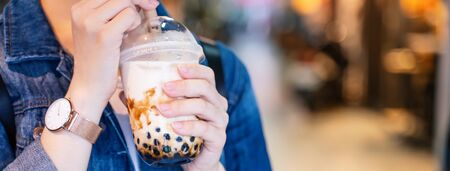 Young girl in denim jacket is drinking brown sugar flavored tapioca pearl bubble milk tea with glass straw in night market of Taiwan, close up, bokeh Reklamní fotografie - 129677375
