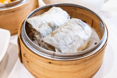 Delicious Lo Mai Gai dim sum, fresh steamed glutinous rice with chicken roll wrapped by lotus leaf in bamboo steamer in hong kong yumcha restaurant. Stock Photo