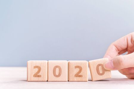 Abstract 2020 & 2019 New year countdown design concept - woman holding wood blocks cubes on wooden table and blue background, close up, copy space.