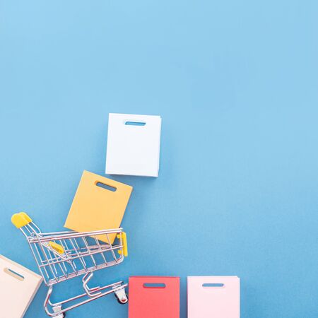 Abstract design element, concept of annual sale, shopping season - mini yellow cart with paper bag isolated on pastel blue background, top view, flat lay. Фото со стока